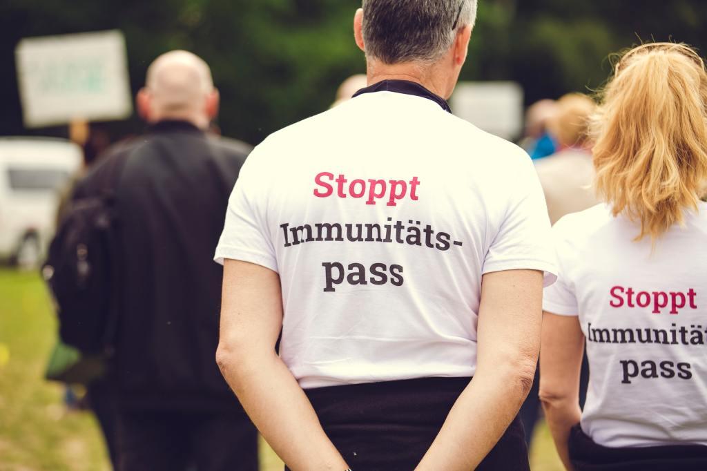 """Ein Mann und eine Frau tragen """"Stoppt Immunitätsausweis""""-T-Shirts"""