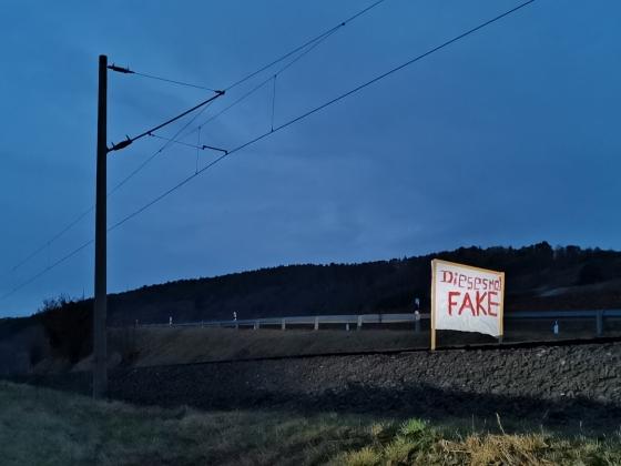 """Ein Plakat auf Holzrahmen in einem Gleisbett, auf dem in roter Farbe """"Diesesmal FAKE"""" steht."""